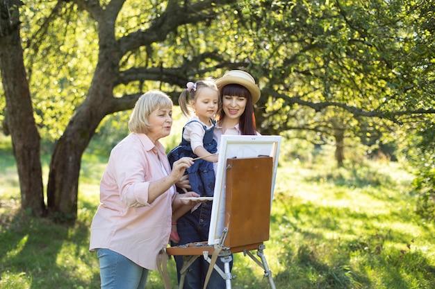 Счастливого семейного отдыха, вместе рисовать. довольно старшая бабушка, молодая мама и дочка маленького ребенка, рисование вместе в солнечный день в красивом летнем саду на мольберте.