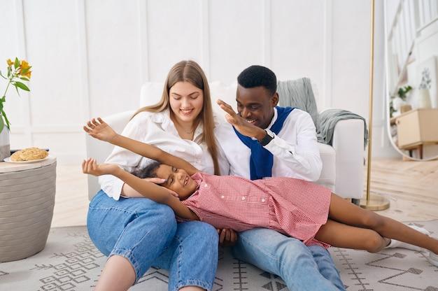 거실에서 행복한 가족 여가. 어머니, 아버지와 딸이 함께 집에서 포즈를 취하고 좋은 관계