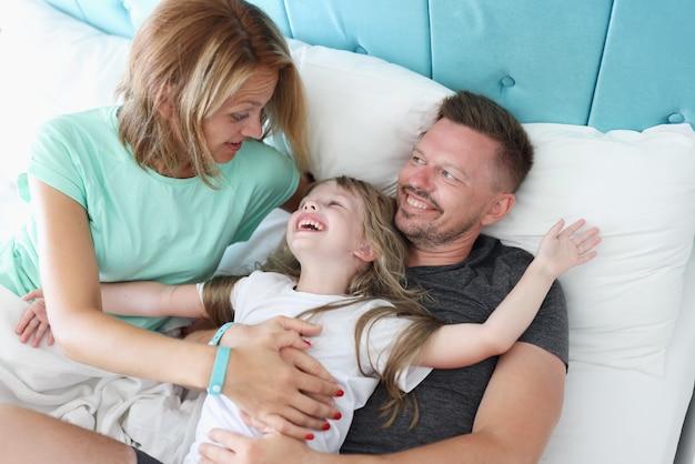 幸せな家族はベッドにあり、笑顔で見てください。