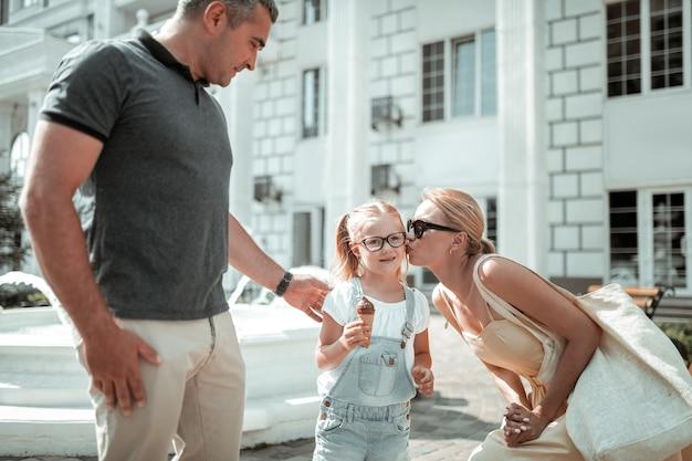 幸せな家族。彼女の母親が彼女にキスし、父親が散歩中に彼女の肩を保持している間、アイスクリームコーンを保持している少女。
