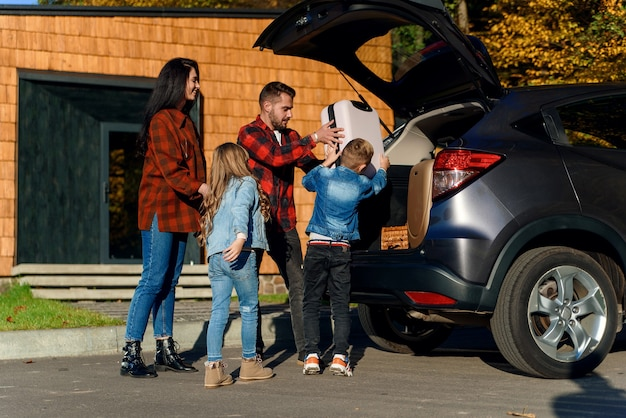 A happy family loads luggage into the trunk of a car when going on a family vacation.