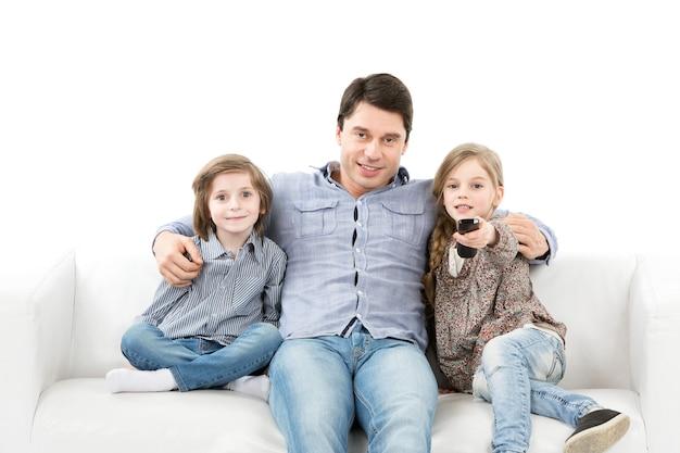 Счастливая семья, глядя на камеру, сидя на изолированном диване. смотря телевизор.