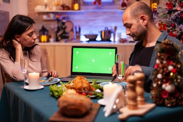 녹색 화면을 보고 있는 행복한 가족은 격리된 디스플레이가 있는 크로마 키 태블릿을 조롱합니다.