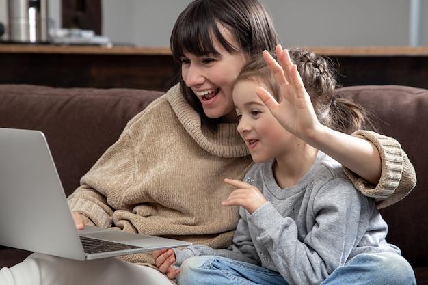 노트북 화면을보고 행복 한 가족 거리 화상 통화를합니다. 웃는 어머니와 어린 소녀가 인터넷 채팅에 webcamera 얘기.