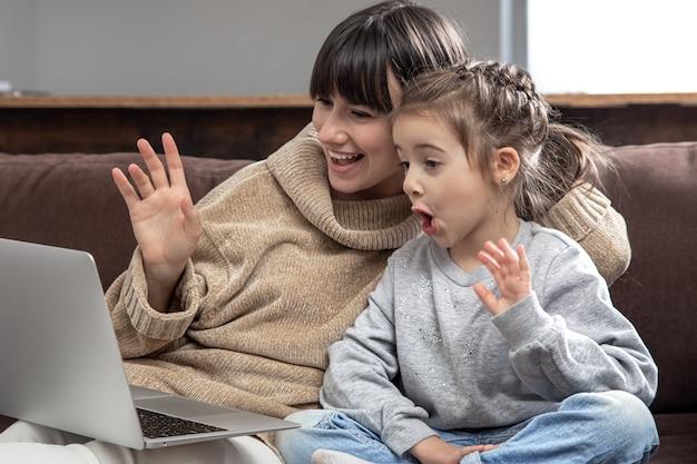 ノートパソコンの画面を見ている幸せな家族は、距離ビデオ通話を行います。インターネットチャットでウェブカメラに話している笑顔の母と少女。