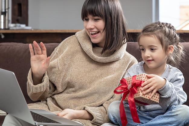 ノートパソコンの画面を見ている幸せな家族は、距離ビデオ通話を行います。ウェブカメラで話しているギフトボックスを持つ笑顔の母と少女。