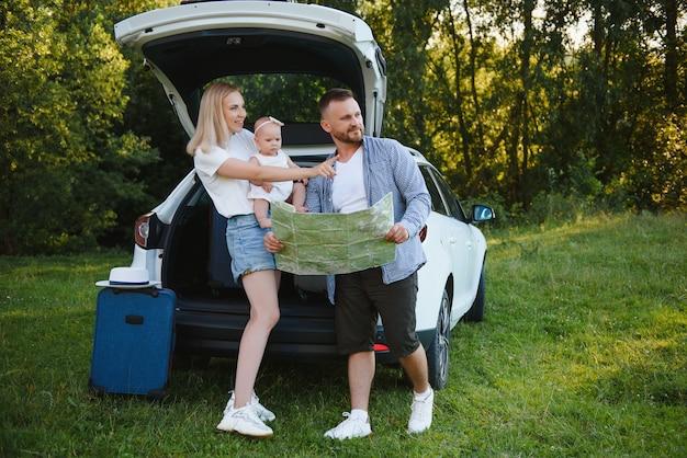차 옆에 있는 지도를 보고 있는 행복한 가족