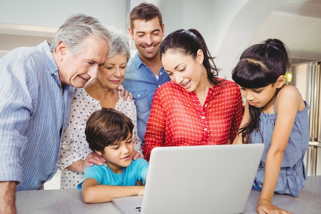 Happy family looking at boy using laptop