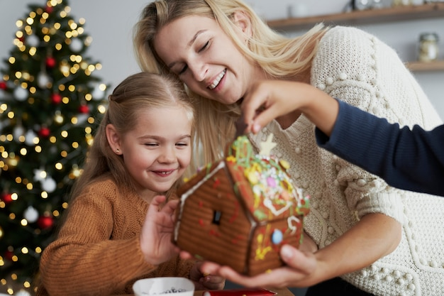 Happy  family looking at decorated gingerbread house