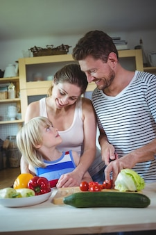 Happy family looking at each other while preparing salad in the kitchen