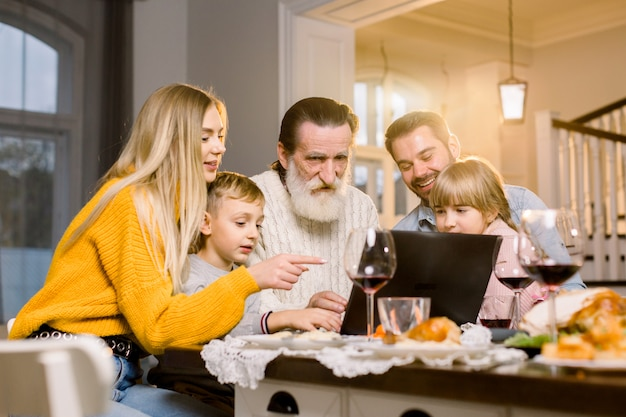 Happy family looking film or making call via internet using laptop, sitting at the festive tabe at home, celebrating dinner together. thanksgiving day concept