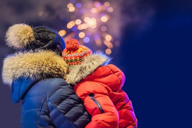 Счастливая семья, глядя фейерверк в вечернем небе