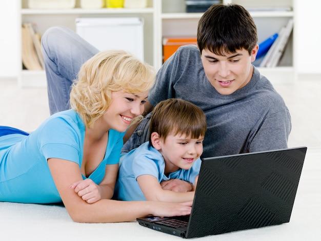一緒にノートパソコンを見て幸せな家族