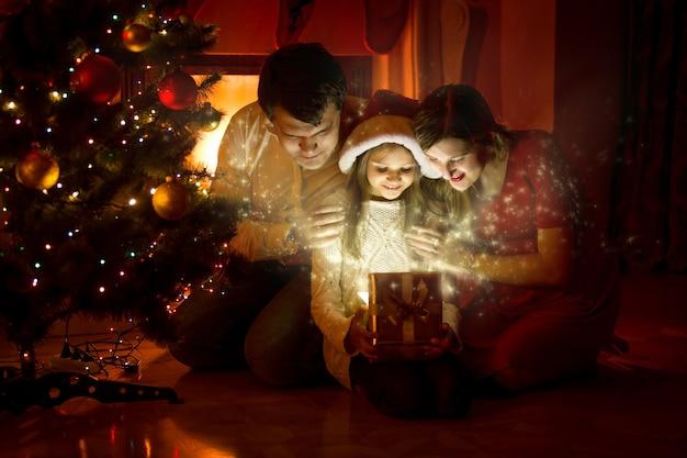 마법의 크리스마스 선물 상자 안을 보고 있는 행복한 가족