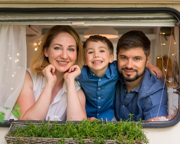Happy family looking out of a caravan's window