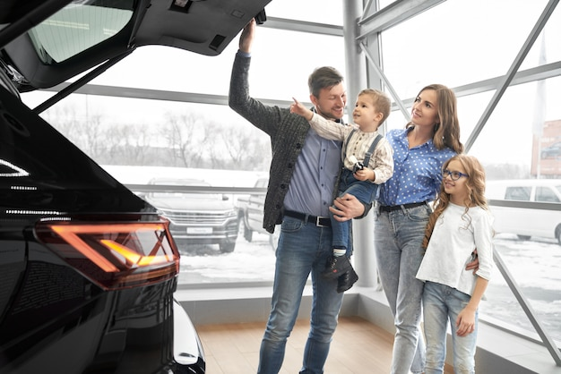 Happy family looking at trunk of expensive black car.