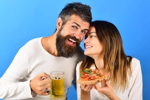 행복한 가족, 함께 피자를 즐기는 사랑스러운 커플. 레저, 음식, 음료, 사랑 개념 - 남편과 아내가 피자를 먹고 있습니다. 웃는 행복한 남자와 여자. 웃고 피자를 먹고 맥주를 마시는 커플