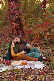 幸せな家族、恋人、夫と妻がカボチャ、リンゴ、お茶とセナピクニックに抱いて