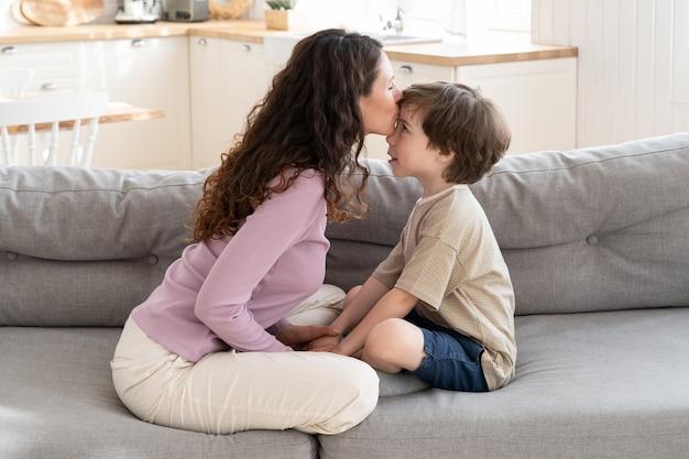 Счастливая семья, любящая мама, целуя маленького сына в лоб, сидя со скрещенными ногами на диване у себя дома