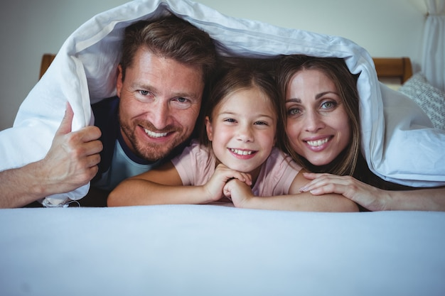 Happy family lying under a blanket on bed
