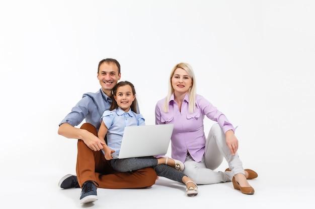 흰색 위에 격리된 노트북으로 온라인으로 인터넷 서핑을 하는 동안 행복한 가족이 바닥에 누워 있습니다.