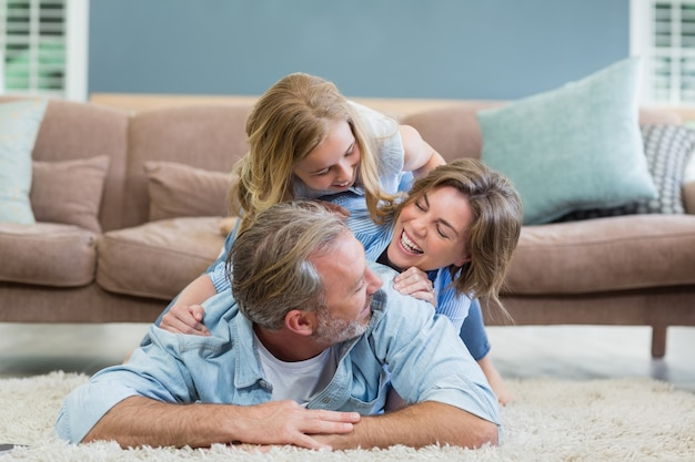 Happy family lying heaped on carpet in living room