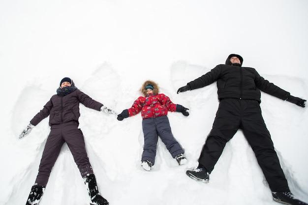 Счастливая семья, лежа в снегу, делая снежных ангелов
