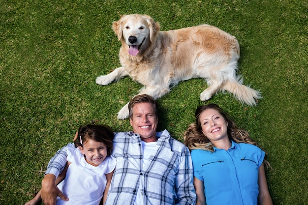 Happy family lying ion grass with their dog