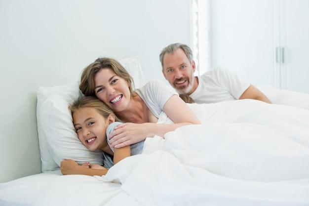 自宅の寝室のベッドに横たわっている幸せな家族