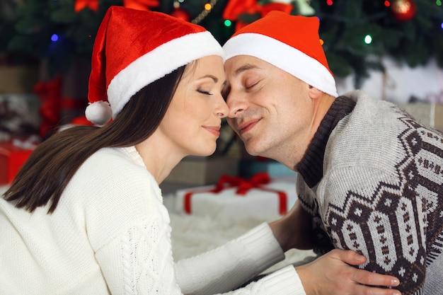 クリスマス ツリーのカーペットの上に横たわる幸せな家族