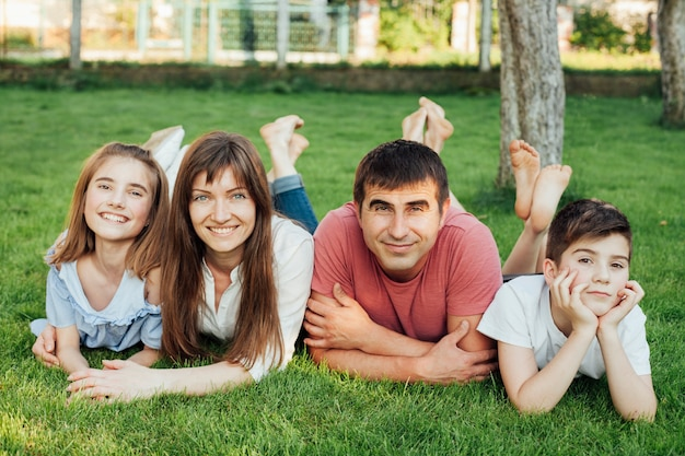 푸른 잔디에 누워 카메라를보고 행복한 가족