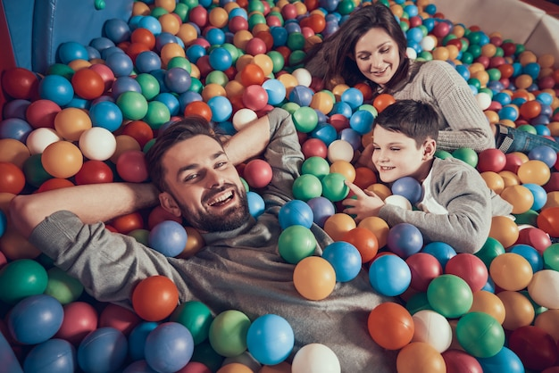 Happy family lying in pool with balls in mall.