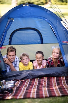 Happy family lying in a tent