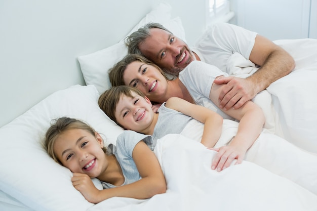 Happy family lying together on bed in bedroom at home