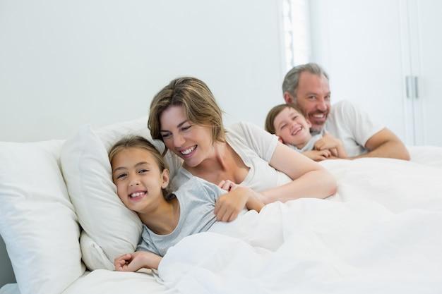 自宅の寝室でベッドに一緒に横になっている幸せな家族