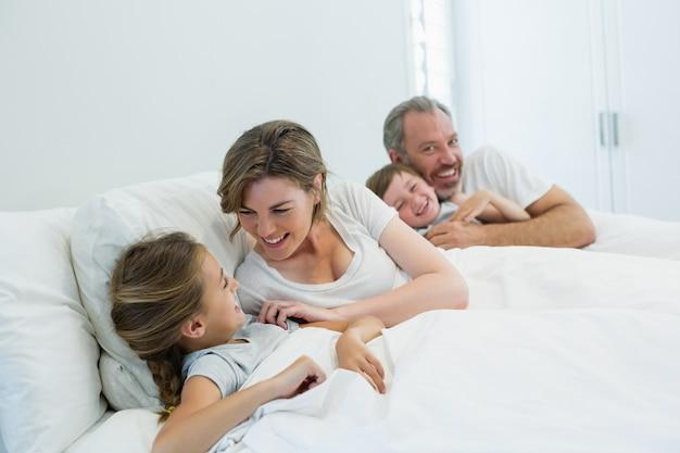 寝室のベッドで一緒に横になっている幸せな家族