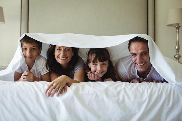 自宅のベッドに毛布の下で横になっている幸せな家族