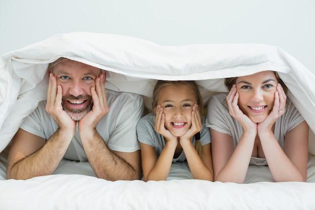 自宅のベッドの毛布の下で横になっている幸せな家族