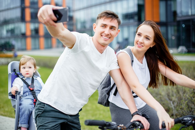 A happy family makes selfie on a smartphone while walking on bicycles
