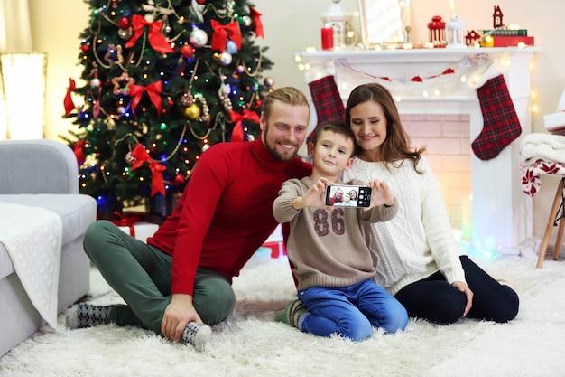 幸せな家族が家の休日のリビングルームで写真を作る