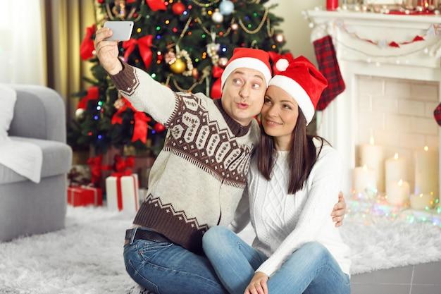 幸せな家族はクリスマスツリーの背景に写真を作る