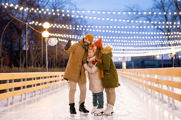 Happy family making selfie portrait on mobile phone while skating on ice rink