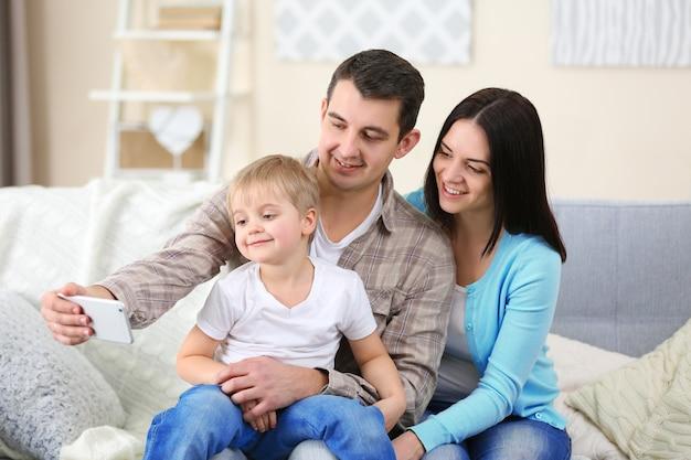 ソファ、屋内で携帯電話で自分撮りを作る幸せな家族