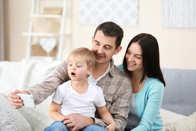 室内のソファで携帯電話を使って自撮りをする幸せな家族