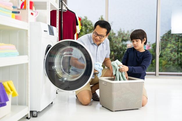 Счастливый семьянин отец-домохозяин и маленький помощник сына-ребенка веселятся и улыбаются, стирая белье со стиральной машиной