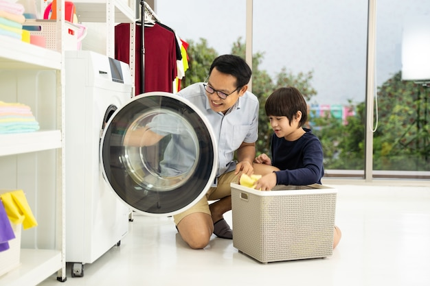 Happy family man father householder and child son little helper are having fun and smiling while doing laundry with washing machine