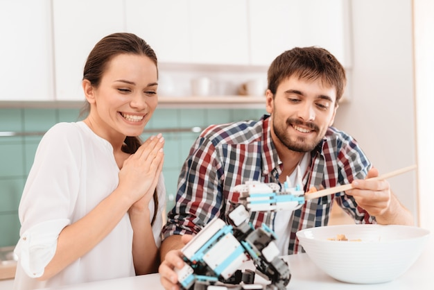 Happy family. man feed robot. spoon with salad.