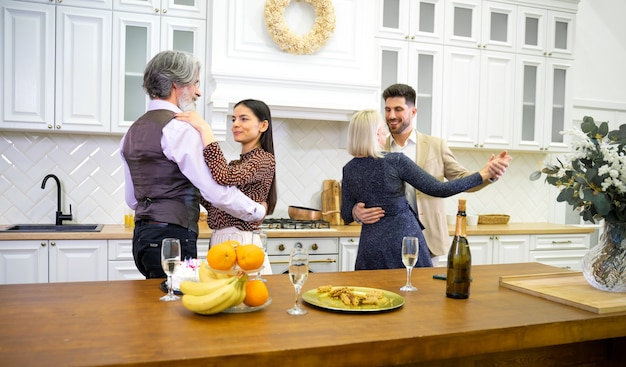 Happy family members dancing during birthday celebration in kitchen near table