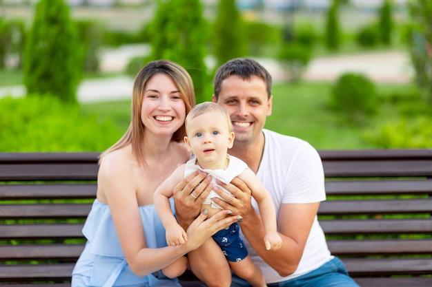 공원에 있는 행복한 가족 엄마와 아빠는 야외 벤치에 앉아 팔에 아기를 안고 즐거운 시간을 보내고 있습니다.