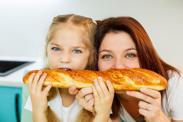 幸せな家族、お母さんと娘は、さまざまな側面から噛んで1つのパンを食べます。子供の家族関係と両親